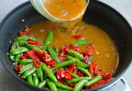 Camarones con ajo y naranja agregando salsa de salteado de naranja a la sartén junto con las verduras
