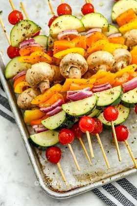 Brochetas de verduras marinadas con hierbas apiladas en una bandeja.
