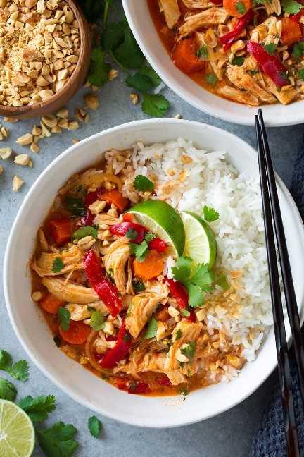 Una foto cenital de Slow Cooker Thai Chicken Curry en un tazón blanco cubierto con rodajas de limón