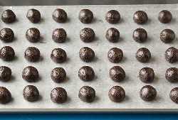Oreo trufado recheio enrolado em bolas em uma assadeira pronta para ser mergulhada em chocolate