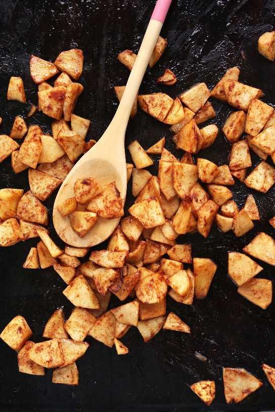 Revuelva manzanas en una bandeja para hornear para un refrigerio vegano casero