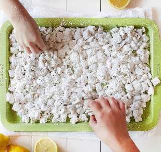 Manos de niños Comiendo Lemon Puppy Chow
