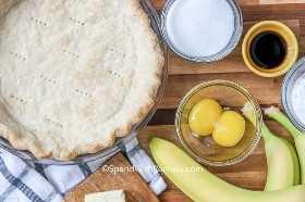 Imagen de arriba de los ingredientes de Banana Cream Pie en una tabla de cortar.