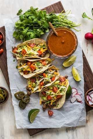 Tacos de carne de res en tortillas de maíz suaves cubiertas con lechuga, tomates y queso junto al tazón de salsa roja.
