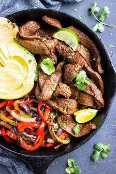 Una sartén grande de hierro fundido con una receta fácil de fajita de carne y verduras.