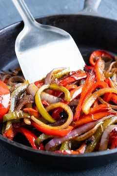 Vegetales salteados para una receta de fajita en una sartén de hierro fundido.