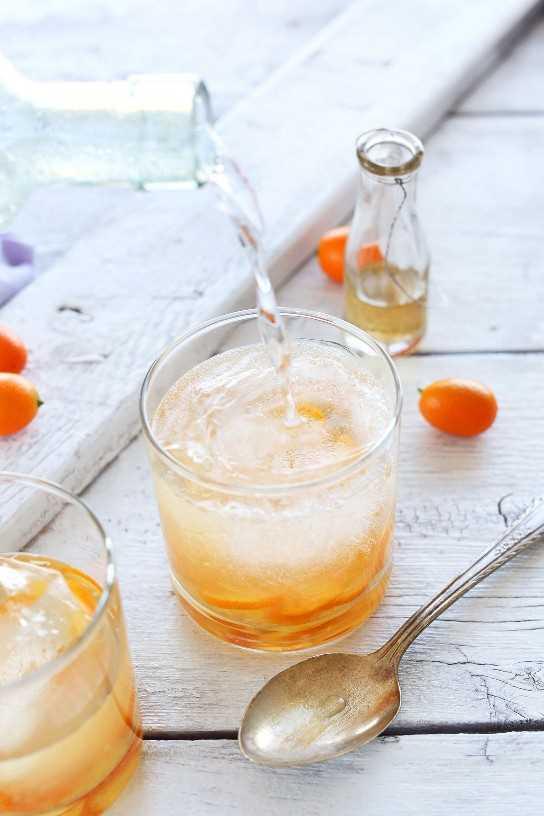 Verter agua con gas en un vaso para hacer un gin-tonic de cítricos totalmente natural casero