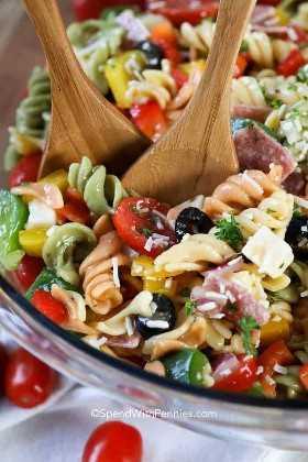¡Un cuenco lleno de coloridas ensaladas de pasta italiana listas para una fiesta!