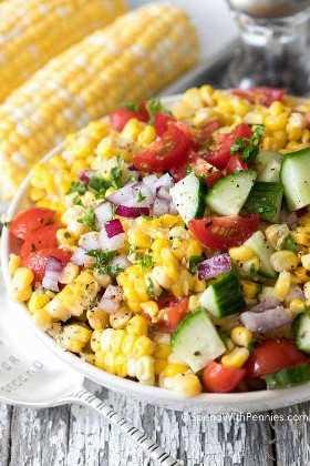 Ensalada de maíz de verano con tomates y pepinos en un recipiente.