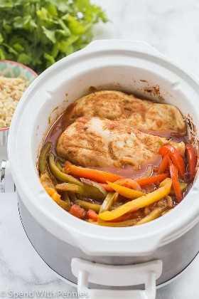 Fajitas de pollo con pimientos y una salsa que se cocina en una olla blanca con arroz y cilantro al lado