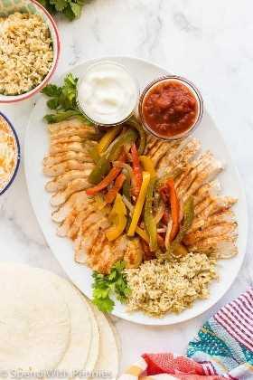 fajitas de pollo crockpot con pimientos, salsa y crema agria en bandeja blanca con arroz y tortillas en el fondo