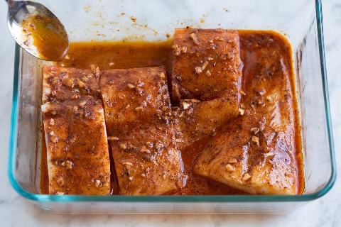Cuchara marinada sobre pescado en una fuente para horno.