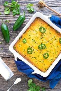 Una fuente blanca para hornear con una receta casera de pan de maíz con jalapeños y maíz.