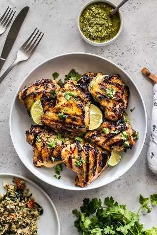 Pollo con lima y cilantro en un tazón blanco grande cubierto con cilantro picado y gajos de lima.