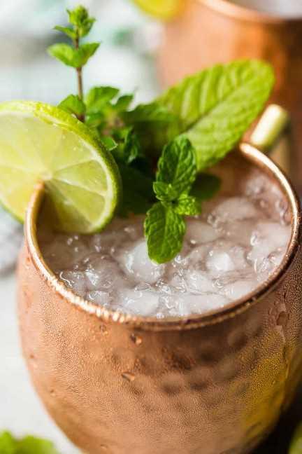 Ciérrese encima de la imagen de una bebida de la mula de Moscú con hielo picado, zumo de lima y menta fresca.