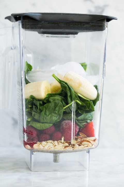 Ingredientes de batido verde en una jarra de la licuadora antes de mezclar.