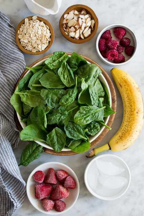 Los ingredientes necesarios para hacer el batido verde que se muestra aquí incluyen espinacas, fresas, frambuesas, plátanos, almendras, avena, agua y hielo.