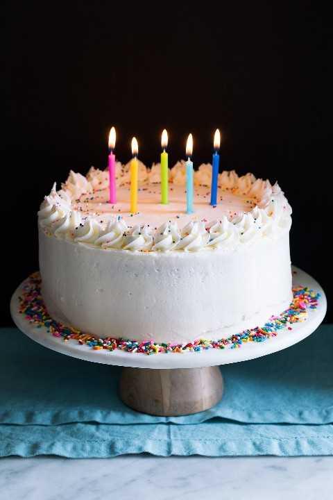 Todo el pastel de cumpleaños en un puesto de pastel adornado con chispas y cubierto con velas de cumpleaños encendidas.