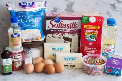 Los ingredientes de la torta de cumpleaños Funfetti incluyen harina para pasteles, mantequilla, azúcar, huevos, claras de huevo, vainilla, extracto de almendras, leche, espolvoreadas, aceite vegetal, crema, sal, levadura en polvo y azúcar en polvo.