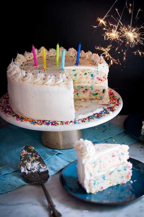 Pastel de cumpleaños cubierto con velas y bengalas a un lado.