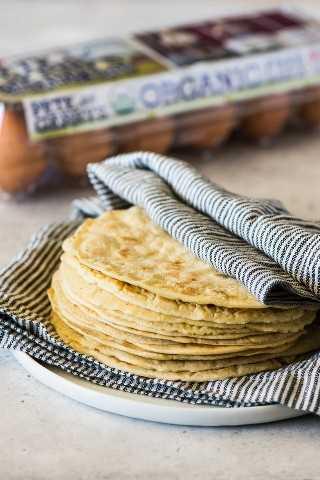 Una pila de paleo tortillas cubiertas con una toalla de cocina limpia.