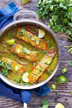 Tailandés de leche de coco al curry con salmón y limón en una sartén de acero inoxidable.