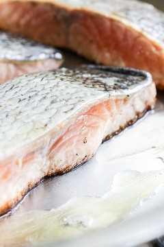 Um filé de salmão cru em uma frigideira de aço inoxidável.
