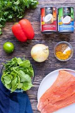 Leche de coco, salmón, espinacas, especias de curry y lima en una tabla de madera como ingredientes para una receta de curry de salmón.
