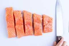 Um grande bife de salmão cortado em 5 porções em uma tábua branca.