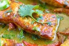 Solomillo de salmón en salsa de curry de leche de coco con una ramita de cilantro encima.