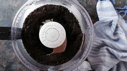Muela finamente las migas de Oreo en el tazón de un procesador de alimentos.