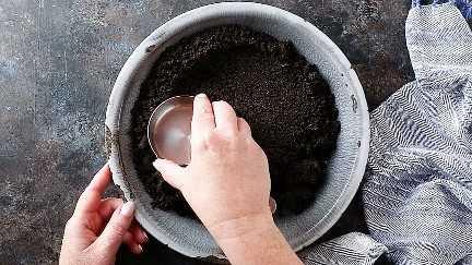 Pressionando a crosta Oreo em uma assadeira com um copo medidor.