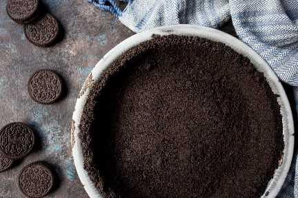 Crosta de Oreo para torta ou cheesecake, sobre um fundo escuro com uma toalha azul.