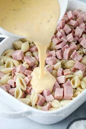 Feche o molho de queijo sendo derramado sobre o presunto e macarrão em uma panela branca.
