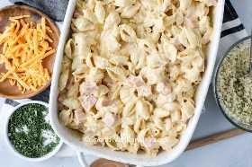 Descripción general de la mezcla de jamón, pasta y salsa de queso en una cacerola blanca con los ingredientes restantes a un lado.