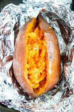 Una batata al horno que se ha cortado por la mitad y tiene sal espolvoreada en la parte superior.