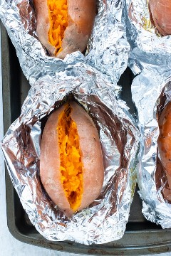 Cuatro batatas que se han horneado en una sartén en el horno.