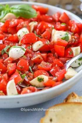 Um prato de salada caprese fresca com uma colher.