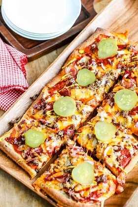 Una pizza de hamburguesa con queso en rodajas sobre una tabla para cortar.
