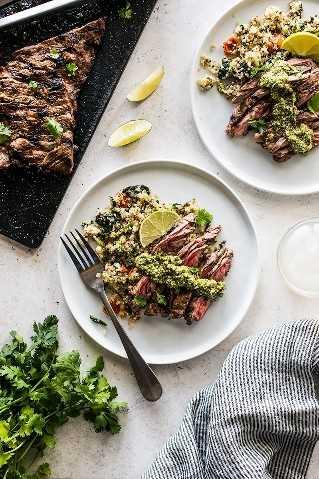 Rodajas de filete de falda a la parrilla en un plato de quinua cubierto con pesto de cilantro