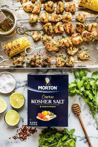 Brochetas de pollo en una bandeja para hornear junto a Morton Coarse Kosher Salt, cilantro, limas y hojuelas de pimiento rojo.
