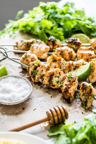 Brochetas de pollo a la parrilla sobre una mesa con cilantro, sal y pimienta.
