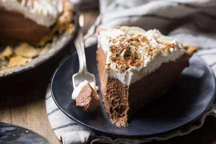 Una rebanada de pastel de crema de chocolate con una mordida eliminada, sobre un fondo de madera oscura.