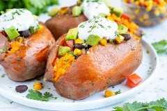Una batata cargada con un relleno de taco mexicano de frijoles negros, tomates, maíz y una mezcla de condimentos para tacos con crema agria en la parte superior.