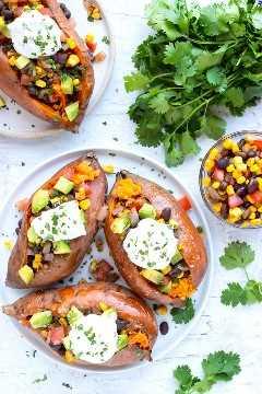 Batatas rellenas mexicanas en un plato blanco junto a un plato de maíz y frijoles negros.