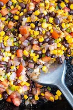 Frijoles negros, maíz, tomates y cebollas, en una sartén de hierro fundido para una receta mexicana.