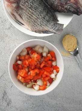 un plato de tomates picados, cebollas, ajo y jengibre y un plato de tilapia cruda a un lado