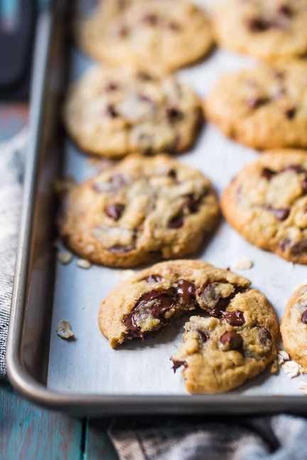 Cerrar imagen de una bandeja de galletas de avena con chispas de chocolate, con una partida por la mitad para mostrar el chocolate derretido dentro.