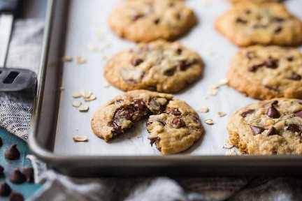 Galletas saludables de avena con chispas de chocolate en una bandeja forrada de pergamino con avena y chispas de chocolate.