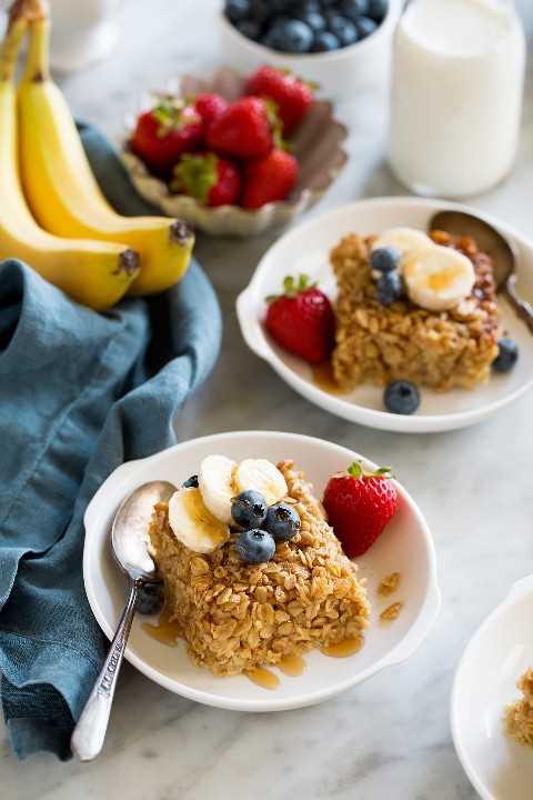 Cuadrados de avena al horno con fruta fresca en tazones blancos.